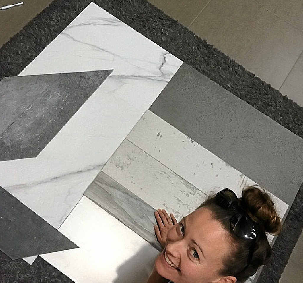 Jess pictured with her tile choices on the left for great bathroom challenge.