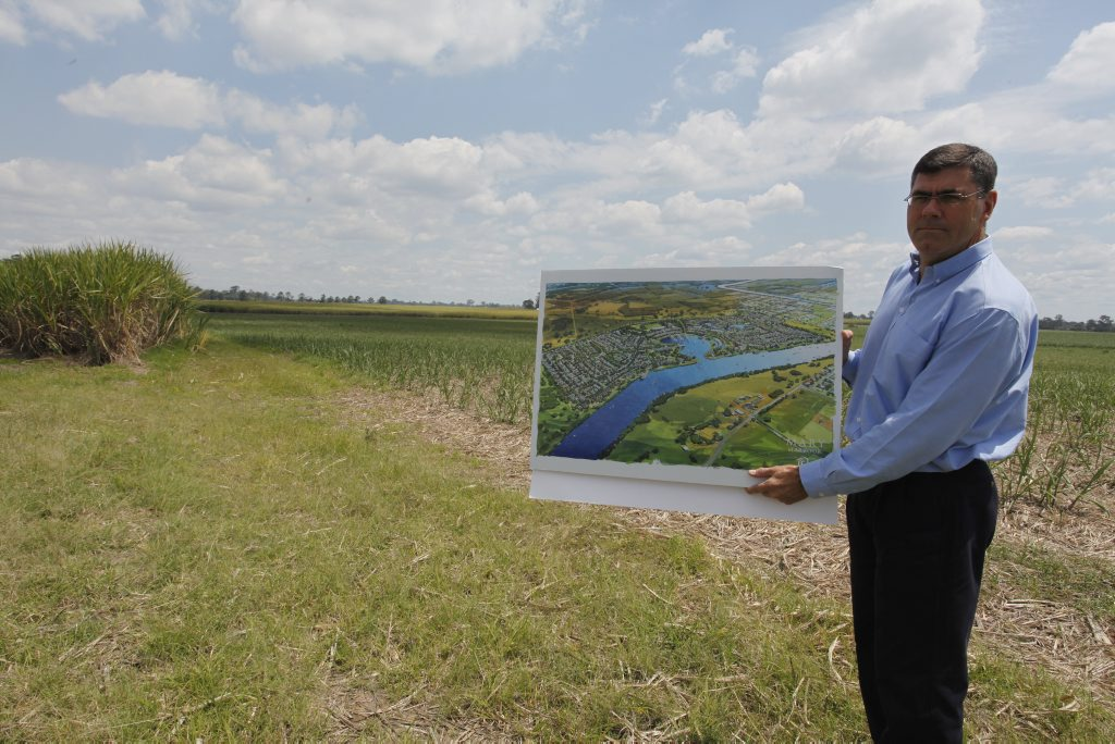 Maryborough Sugar CEO Mike Barry with an artist's impression of the company's proposed $500 million Mary Harbour project at Granville on land that is now under sugar cane. Photo: JOCELYN WATTS 10m949