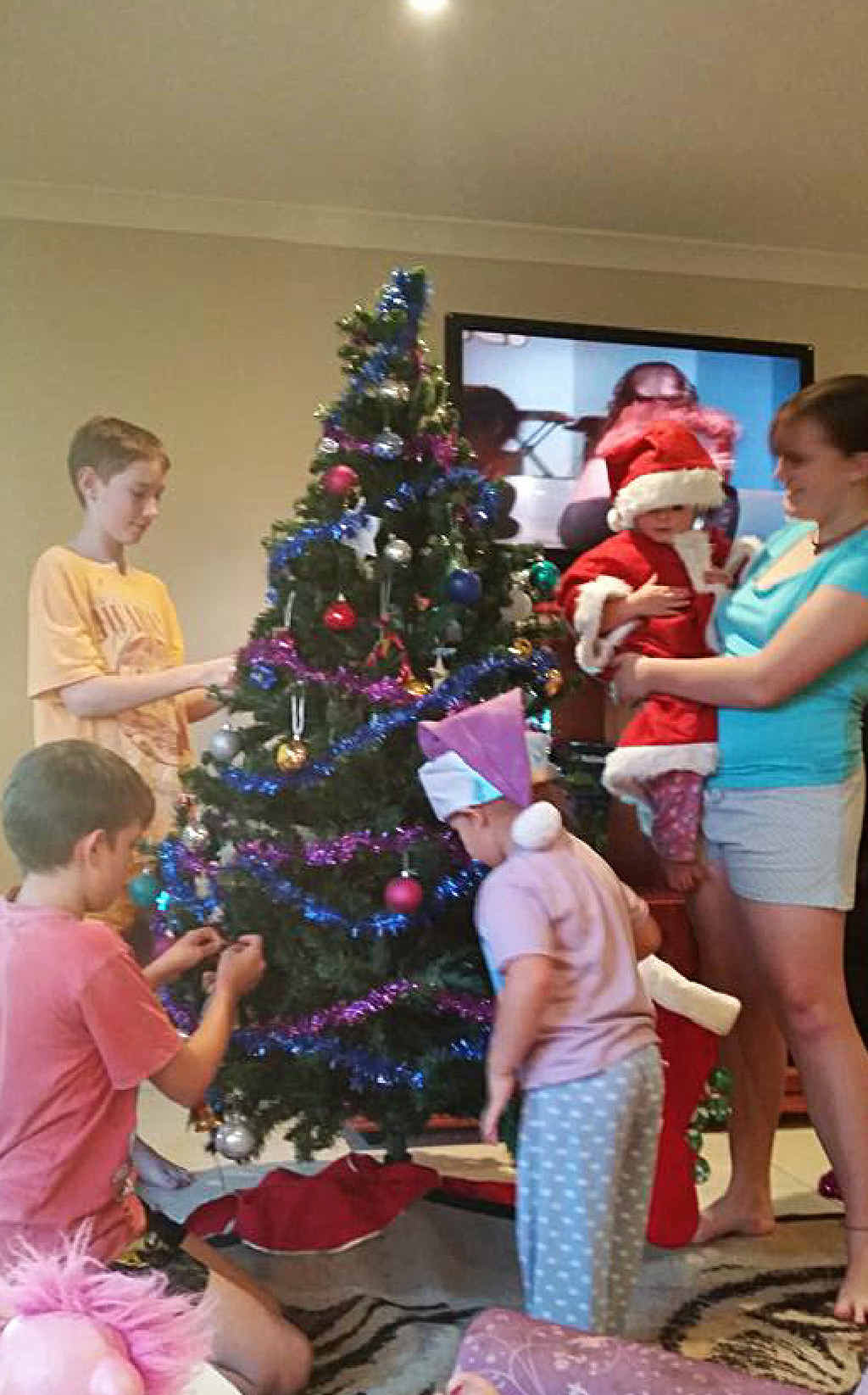 TEAM EFFORT: Tiana McKee supplied this lovely photo of her family gathering to decorate their Christmas tree.