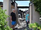 Twin Waters resident Rob Smith and his daughter Hayley Barry-Smith take stock of fire destruction at at Mr Smith's Baywater Dr home.