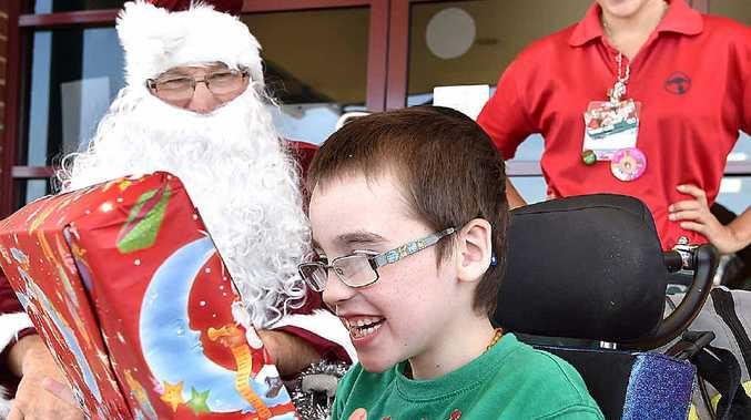 THE BEST MEDICINE: Santa Claus visits Hervey Bay hospital with gifts for children. Jacob Martin, aged seven, receives his present from Santa with elf Stephanie Wailes, from Bunnings, looking on.