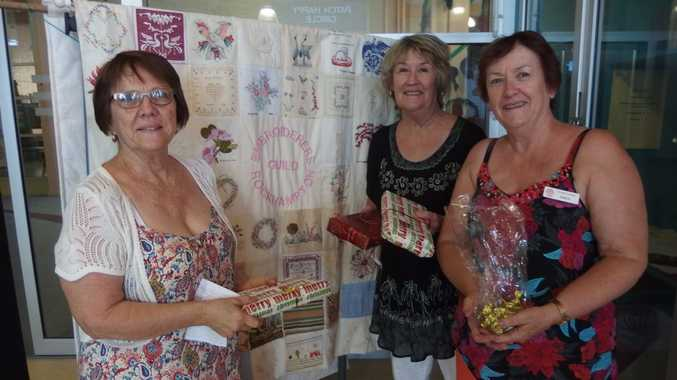 CHRISTMAS CHEER: Embroiderers' Guild Members, Ros Crew, Suzanne Finnigan and Marilyn Bloxsom admiring some of the prizes for the multidraw they held at their Christmas Party to aid the Kalkiah Respite Centre.