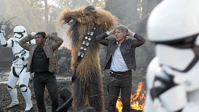 John Boyega, Peter Mayhew (as Chewbacca) and Harrison Ford in a scene from the movie Star Wars: The Force Awakens.
