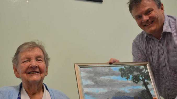TRIBUTE: Peggy Guy hands her painting to her daughter's former boss, Paul Barlow, of accountancy firm Barlow Dolling.