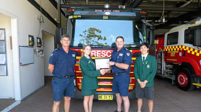 Orara High School captains Anna Fry and Stanley Nelson visit Coffs Harbour Fire Station to present a letter of appreciation for efforts that minimised fire damage to the school.