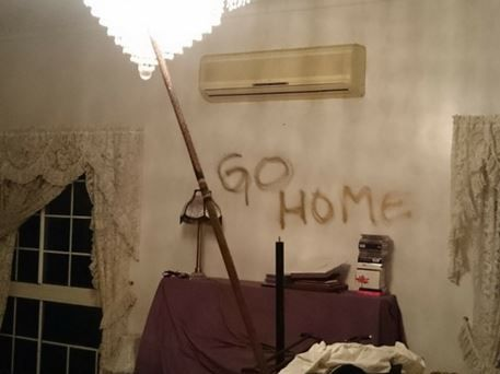 A family has come home to offensive and threatening slurs spraypainted on their walls and fires started on the carpet after marauders took exception to Arabic writing above their front door.