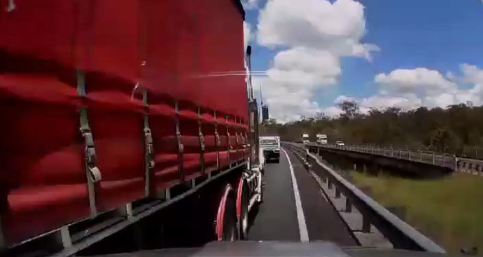 A still image from dash cam footage of a truck sideswiping a Hilux on the Logan Motorway.