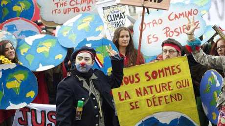 A demonstrator disguised as a clown is seen among thousands demanding climate justice and environment protection in Paris on December 12, 2015. A climate march was organized by several NGOs as COP21 negotiations come to an end.