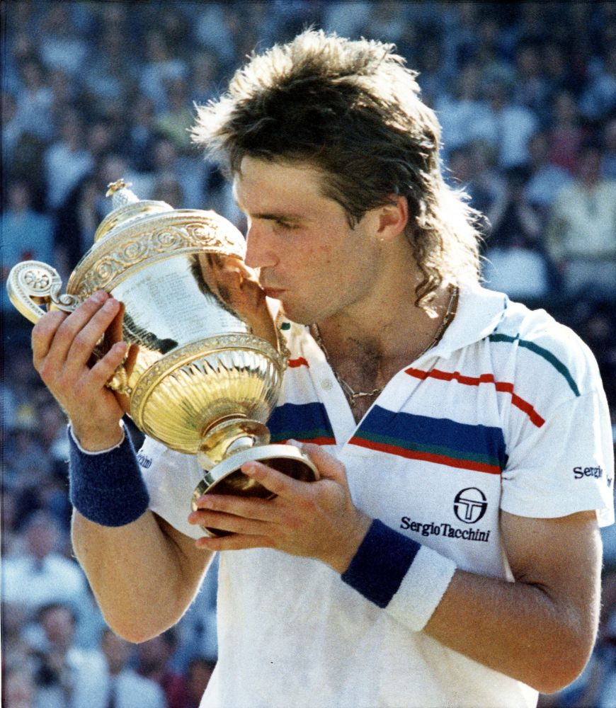Australian Pat Cash, kisses his trophy on the Centre Court at Wimbledon, July 5, 1987, after defeating Ivan Lendl to take the Men's Singles Championship. (AP Photo/Staff/Dear)