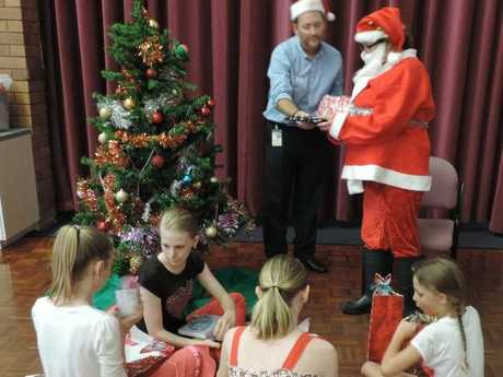 Suncare Community Engagement Manager Graeme Baxter was on hand to help Santa distribute Christmas presents at an afternoon tea celebrating the work of Children in Grandparents Care. Photo Contributed