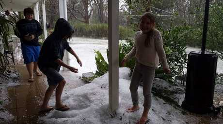 Stanthorpe residents are all smiles as they play in the hail caused by yesterday's storms.