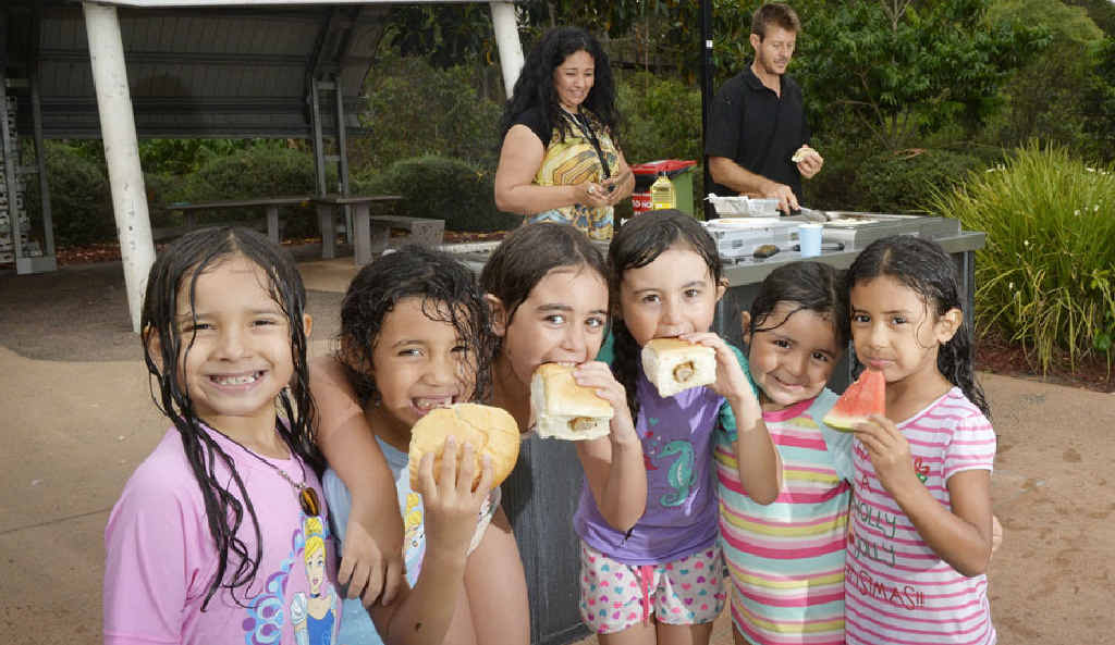 BARBECUE TIME: Yanui and Peter Rea cook up a storm for (front) Kira Smith, Isabella Hurunui, Vettoria Montez, Edith Montez, Anabel Montez and Lucia Hurunui at Robelle Domain on Christmas Eve. More barbecues will fire up today across Ipswich as the community celebrates Boxing Day.