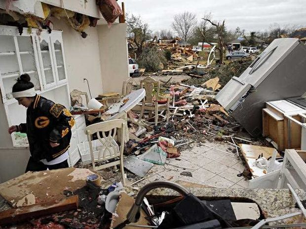 Residents surveyed the destruction from deadly tornadoes in North Texas as the same storm system brought winter woes to the Midwest on Monday, amplifying flooding that's blamed for more than a dozen deaths and prompting hundreds of flight cancellations.