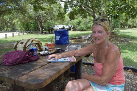 Narangba resident Elayne Mitchelson enjoys doing a crossword at the Freshwater day area at Teewah Beach. Photo Stuart Cumming/ Sunshine Coast Daily