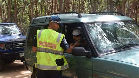 A woman gives a sample of breath during random breath testing on Leisha Track in the Cooloola Recreation Reserve.