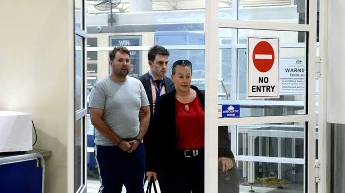 Jason Wayne Greatbatch, 35 from South Australia, arrives at Mackay airport with detectives. He is facing charges including attempted murder for an attack on Teagan Moore at Kuttabul.