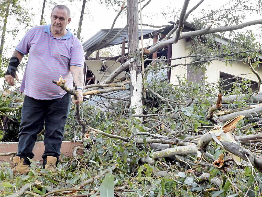NATURE'S FURY: Phil Warr helps out with the clean-up immediately after a mini-cyclone tears through Fernvale and Fairney View.
