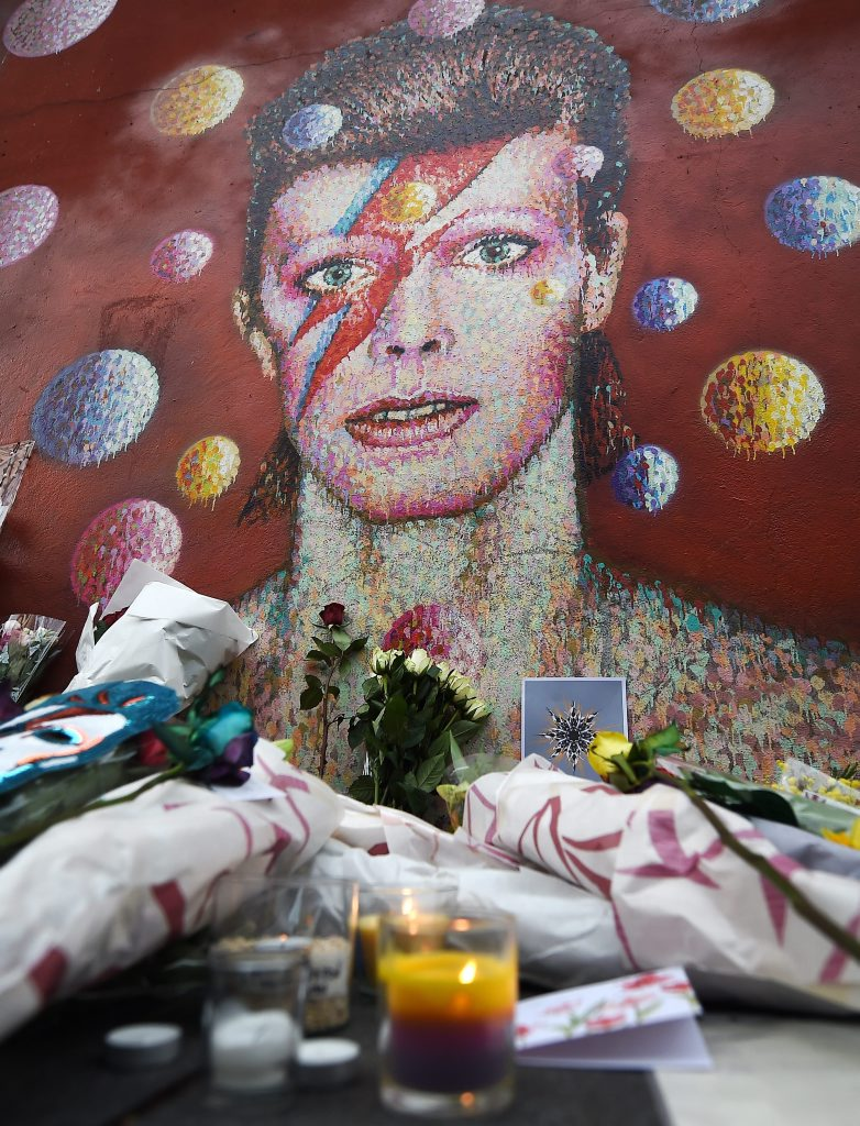 Flowers at a tribute mural for British singer David Bowie in Brixton, birth place of the late David Bowie in London, Britain, 11 January 2016. Well-wishers have flocked to the Bowie mural to pay their respects following the announcement of his death.