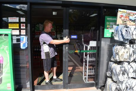 BP Tanawha console operator David Jones inspects damage to a front glass sliding door caused by thieves.