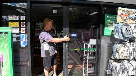 DAMAGE DONE: BP Tanawha console operator David Jones inspects damage to a front glass sliding door caused by thieves.