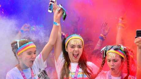 High school friends Kianni Joiner, 13, Bliss Hunter, 12, and Lara Cordwell, 13 dance up a colour storm at Sunshine Coast Stadium.