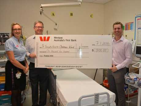 Real Estate Agent Robbie Witt (right) hands over $1400 to St Gabriel's Nurse Unit Manager Sharon Jillett and St Vincent's Director of Clinical Services Jeff Potter. Once donations near $9000, the hospital will purchase a special paediatric treatment bed similar to the one pictured.