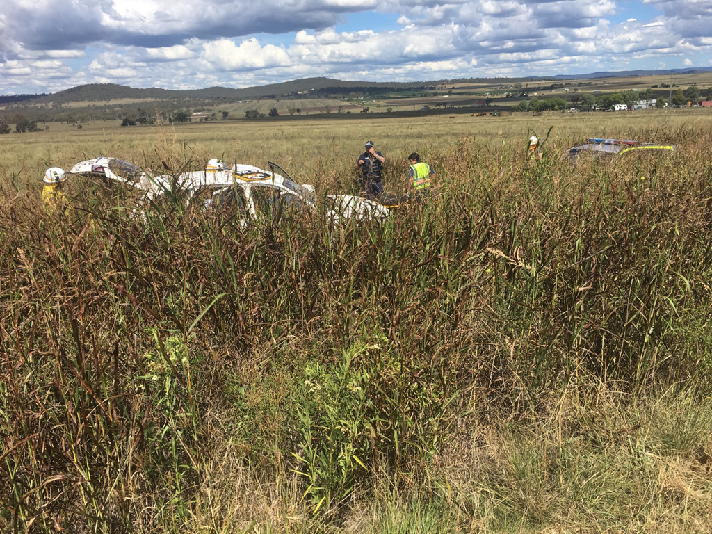 Emergency services work to free an elderly couple trapped in a crash wreckage on the New England Hwy at East Greenmount.