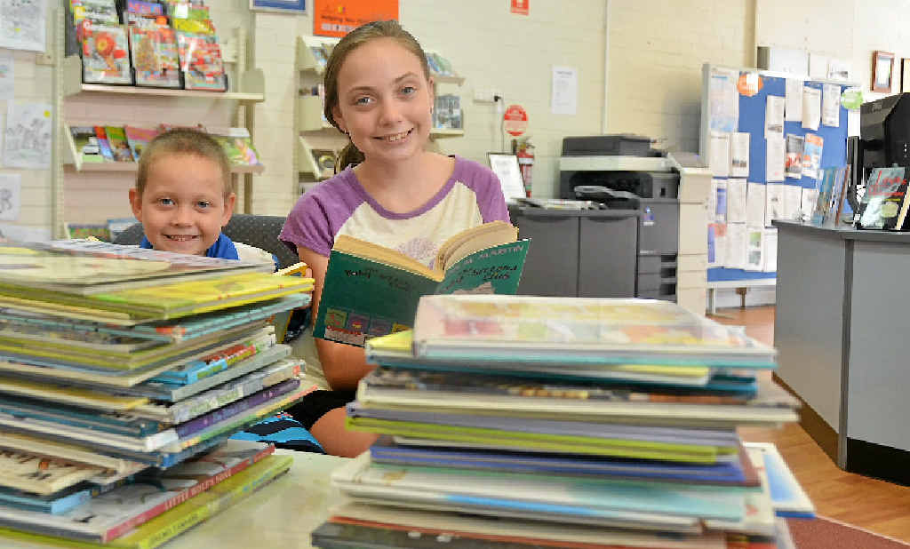 READ AND LEARN: Siblings Hayley and Michael Cook visit the library at least once a week with their parents.