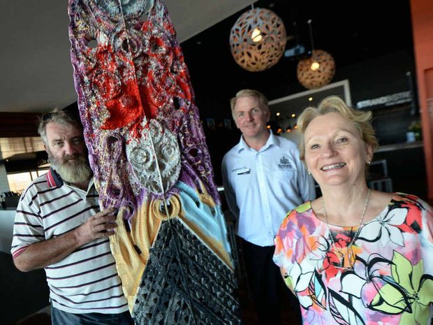 BOARD ART: Artist Tim McGrath, hotel manager Peter Sullivan and Busi Women Inc president Desley Cowley with a carved surfboard made by Tim, which will be hung in the Strand Hotel.