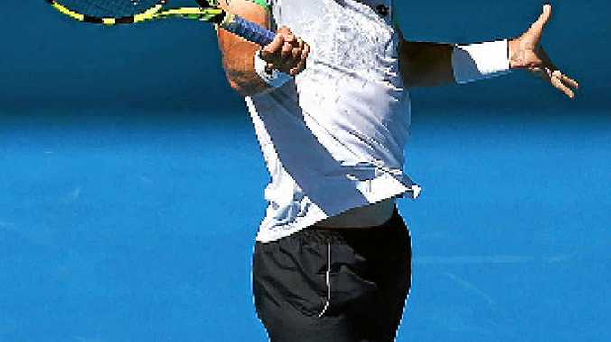 SLAMMIN' SAM: Sam Groth belts a backhand during his first round win over Frenchman Adrian Mannarino yesterday.