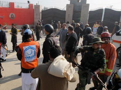 Pakistani troops and rescue workers gather at the main gate of Bacha Khan University Pakistan after gunman attacked killing several people. Photo/Mohammad Sajjad