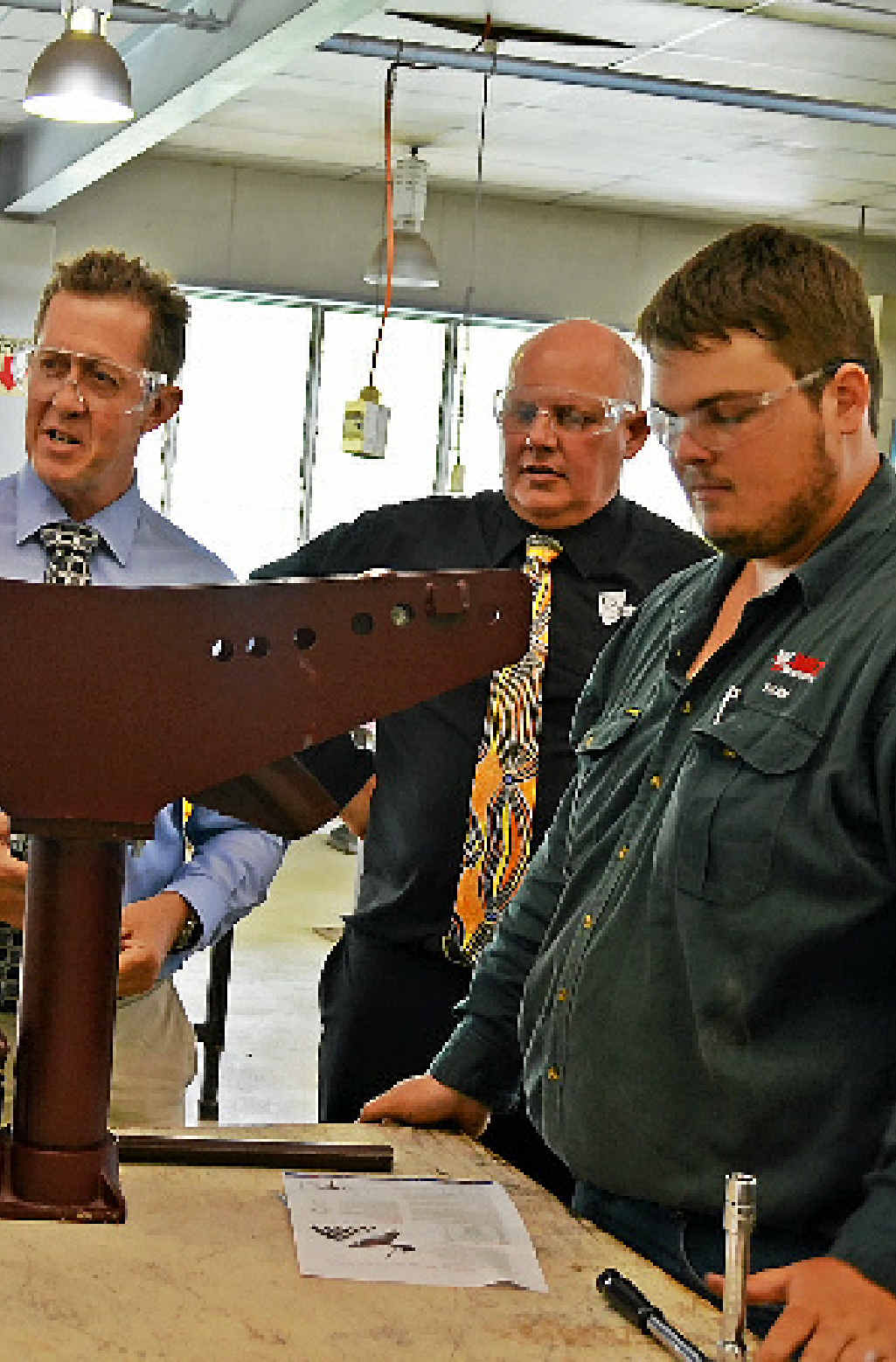 TAFE VISIT: Vocational education minister Luke Hartsuyker (left) and CQUni vice chancellor Scott Bowman inspect a metal fabrication project with apprentice Ryan Young.