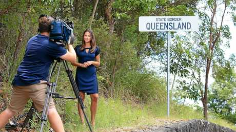 A Channel 7 news crew covers the Queensland Border sign on Kent Street, Coolangatta after it was corrected and replaced today.