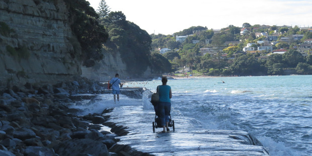 Water starts to lap the woman's feet and her pram as the waves increase in size and ferocity. Photo / Eliane Souza