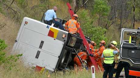 SES and police sit atop a corrective services vehicle that rolled on the Gwydir Highway leaving at least one inmate trapped.