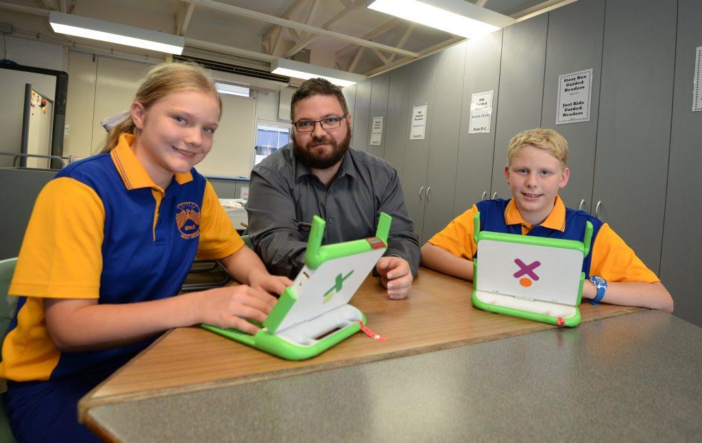 Briella Weber, Paul Corrin deputy principal and Codey Simpson using XO laptops at Mt Archer State School. Photo Allan Reinikka / The Morning Bulletin