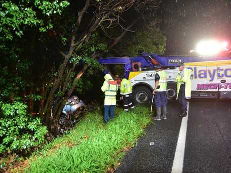 Tow truck drivers attempt to retrieve a car involved in a fatal crash on the Bruce Highway near Pomona.