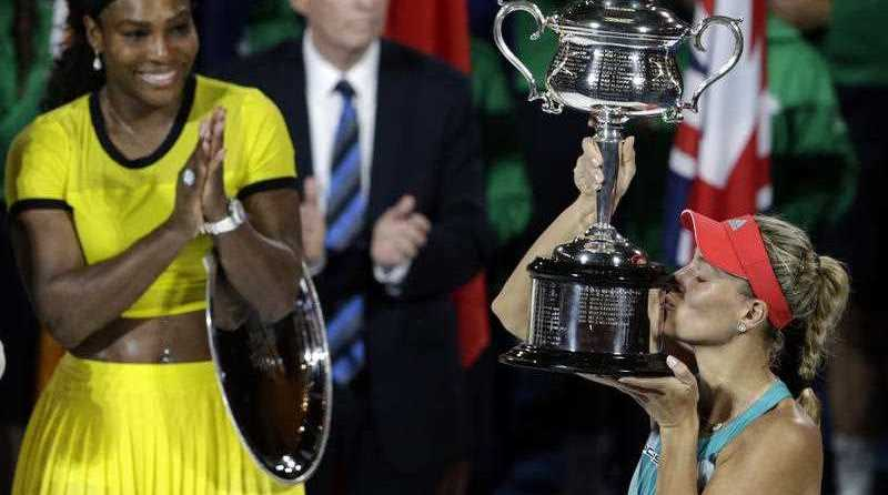 Angelique Kerber of Germany kisses the trophy after winning her final match against Serena Williams of the US at the Australian Open tennis tournament in Melbourne, Australia, 30 January
