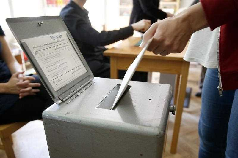 A voter drops in his ballot in an election office in Bern, Switzerland