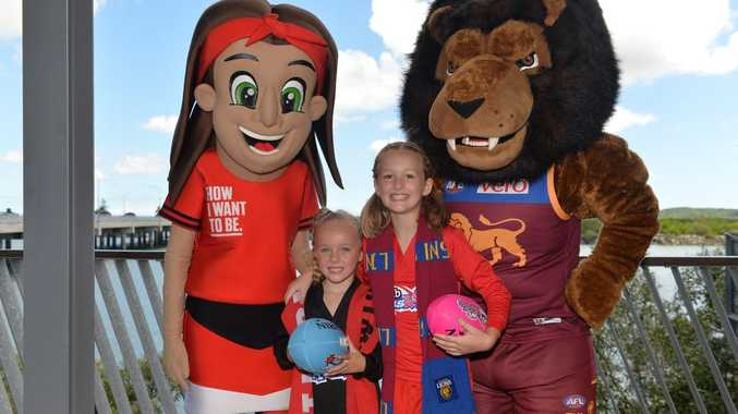 Sisters Allie, 5, and Shannah Grant, 8, with Brisbane Lions mascot, Roy the Lion and Angelica from St Kilda.