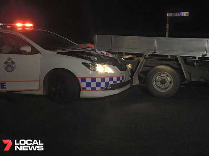 Police car damaged by offender who stole vehicle from Rockhampton, broke into Benaraby home, stabbed resident, drove off and reversed into police car and took off on foot.