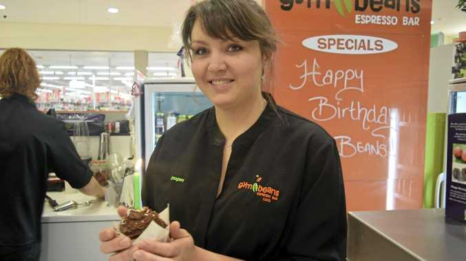 Gym Beans operator Imogen Vicary blows out a candle to celebrate her first anniversary.