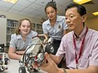 ROBO STUDIES: Eileen Scott (left) and Madeline Saunders are thrilled to get robotics lessons from Yasufumi Kawarada.