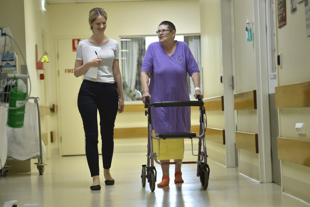 Recovering in Toowoomba Hospital, Meg Hatfield walks down the rehab unit corridors with social worker Meagan Keating.