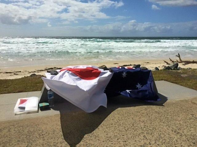 The memorial stone bench covered in a Japanese and Australian flag