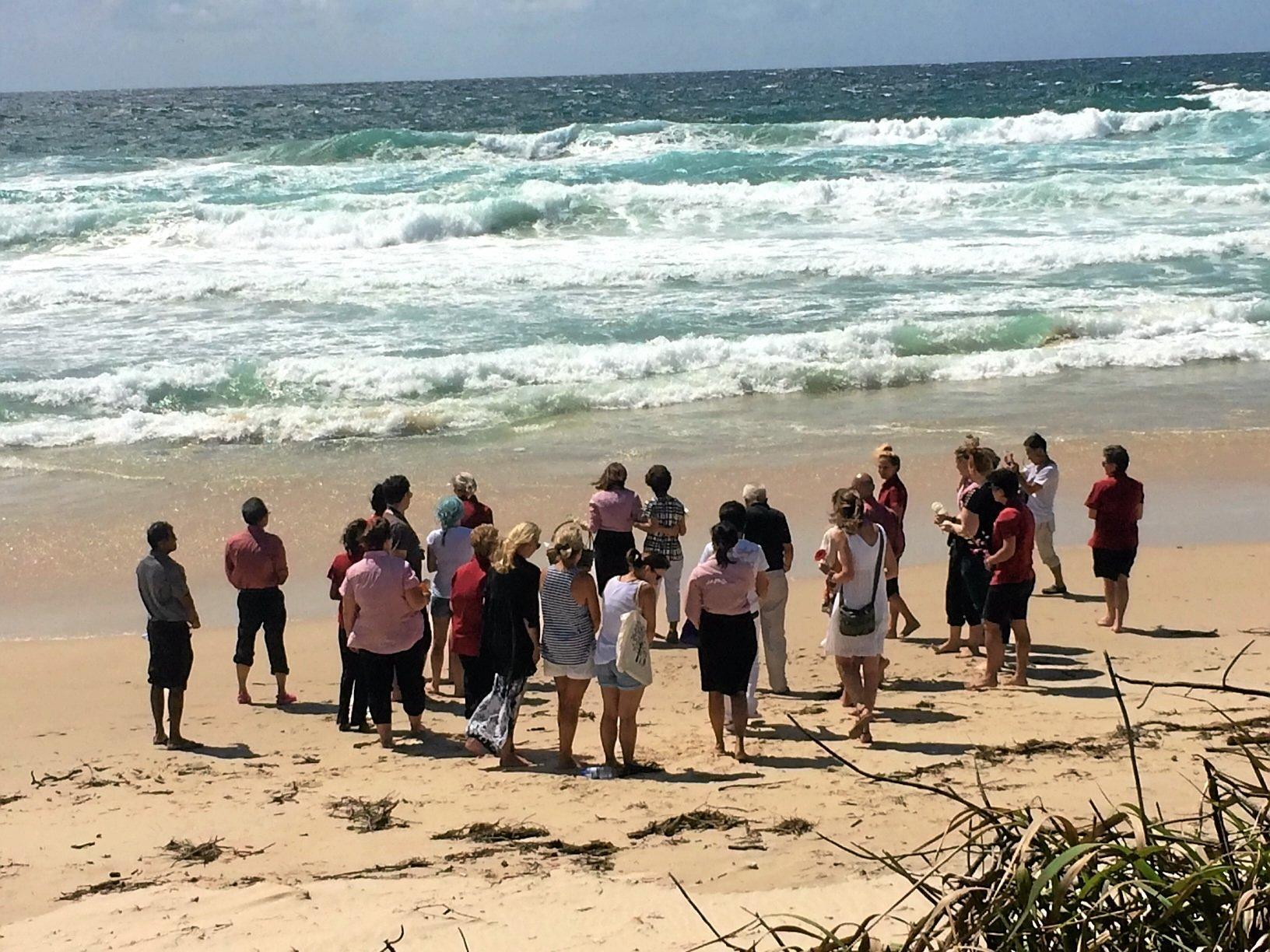 Staff of the Ramada Ballina and Tadashi's family prepare to throw flowers to the ocean to celebrate Tadashi's memory