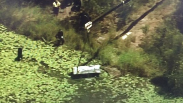 A crane lifts a metal box from a dam at Logan as police search for two bodies. Photo: Nine News Brisbane/Twitter