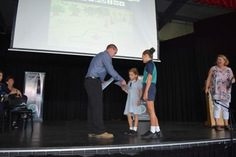 Rowlo Constructions project manager Michael Schulz receives a thank you certificate from Buddina State School students Summer Cash (left) and Dakota Luke.