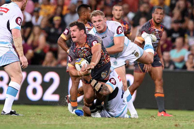Greg Bird of the Indigenous All Stars (centre) is tackled by Tom Burgess of the World All Stars during their annual clash at Suncorp Stadium in Brisbane, Saturday, Feb. 13, 2016.