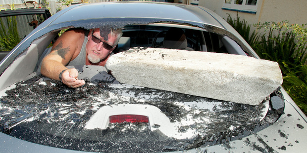 Andy Sinclair with a concrete block vandals used to smash the back window of his car. Warren Buckland/ Hawke's Bay Today